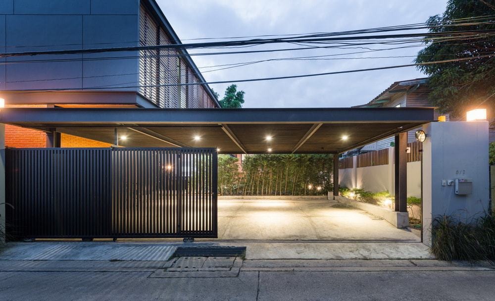 The house has a large metal beam gate the retracts and opens to a wide car port that can fit multiple cars.