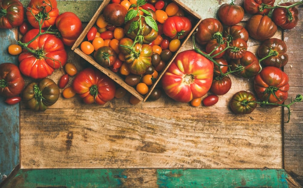 A variety of different tomatoes on a rustic surface.