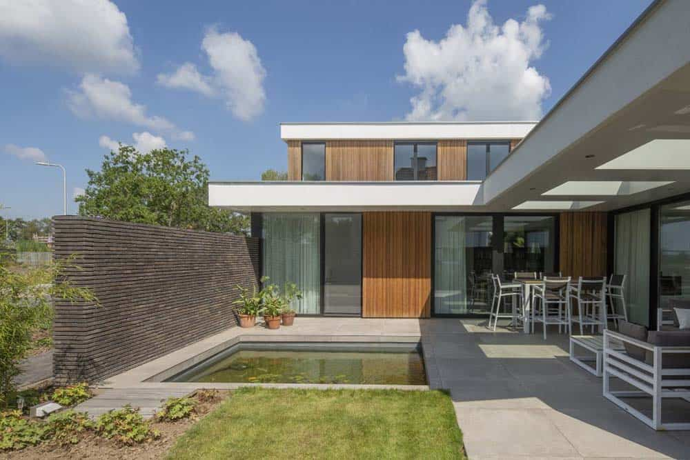 This is a look at the back of the house with a square swimming pool surrounded by concrete walkways and potted plants.