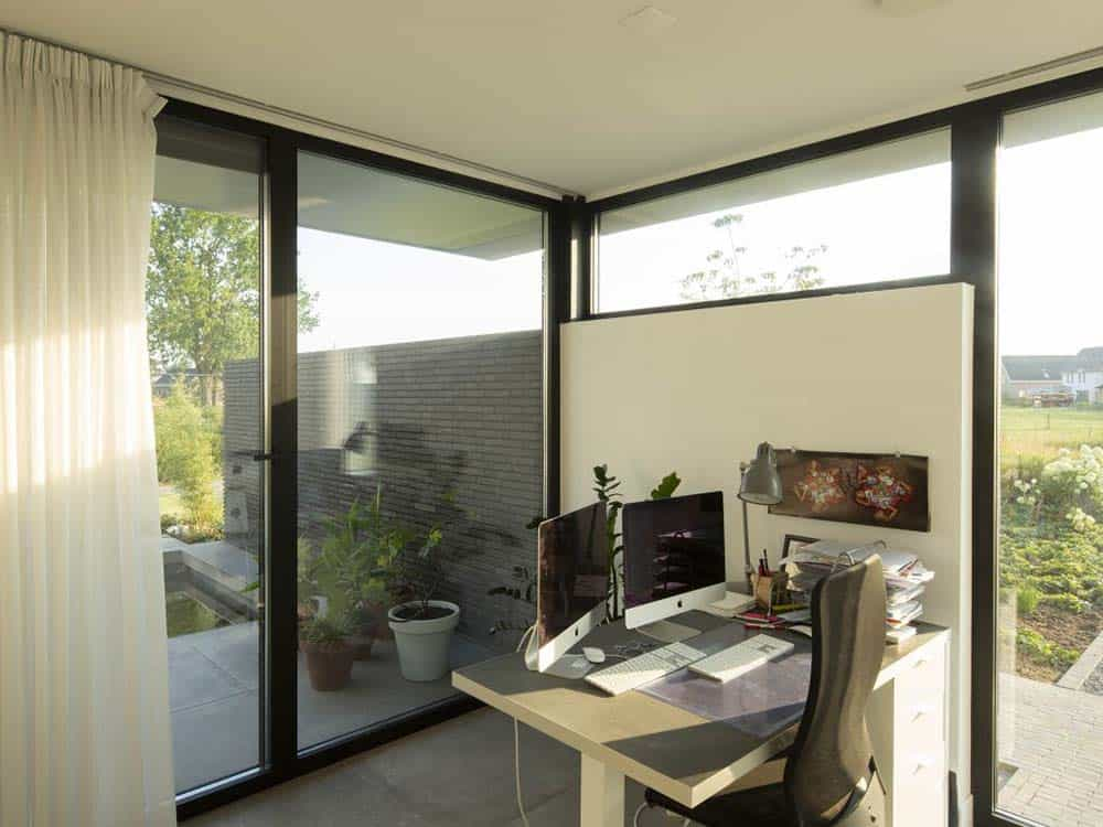 This is the home office that has an abundance of natural lighting because of the glass windows and doors. It also has a simple desk that is built into the wall.