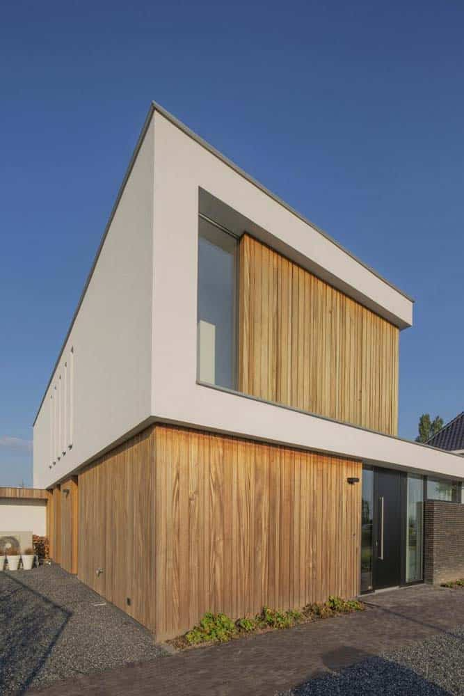 This close look at the house exterior showcases the wooden tone that is complemented by the bright beige tone of the second level of the house.
