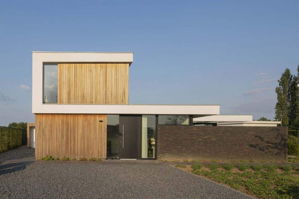 This is a view of the front of the house featuring a wide graveled driveway that matches with the dark textured wall.