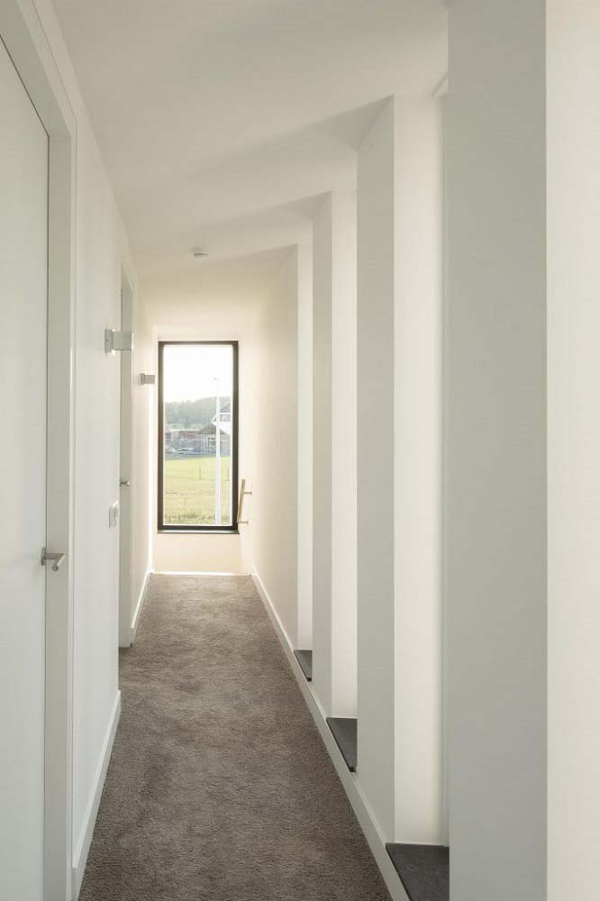 This is a hallway within the house with bright white walls, ceiling and doors illuminated by the natural light coming from the window on the far side.