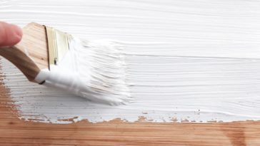 A close look at a piece of wood being painted with white water-based paint.