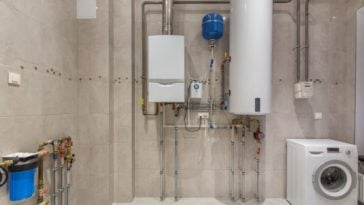 A close look at a laundry room that has a condensing water heater system.