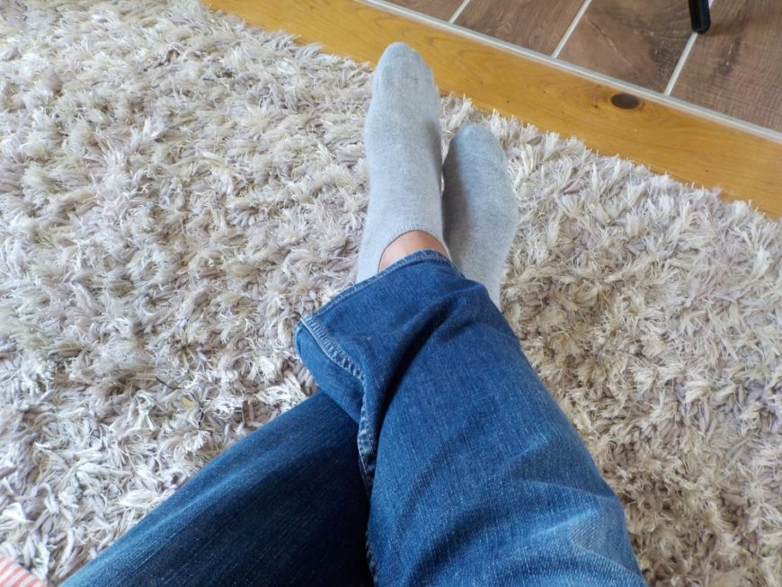 A man's feet with socks on the shag carpet.