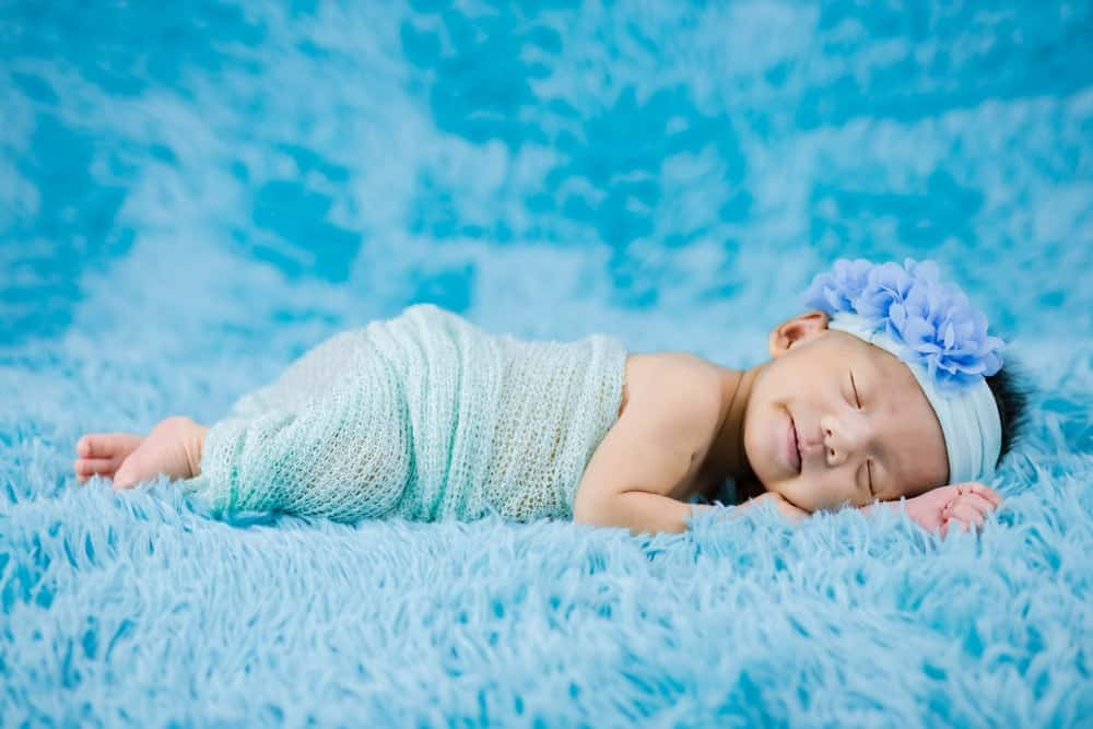 A baby sleeping on a wool shag carpet.