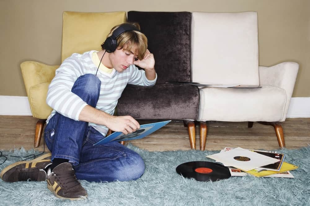 A man relaxing and listening to music on the shag carpet.