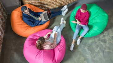 Three people having a meeting while sitting on bean bag chairs.