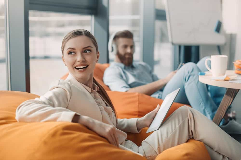 A man and a woman sitting on bean bag chairs at an office setting.