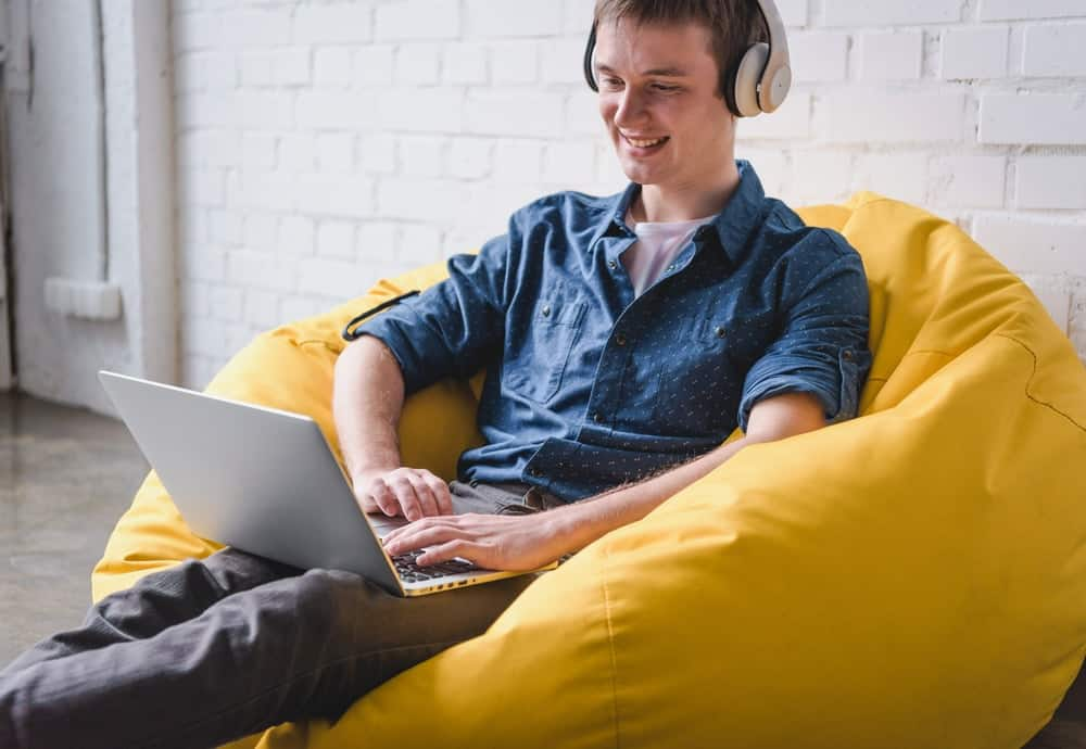 A man working on his laptop while sitting on a bean bag chair.