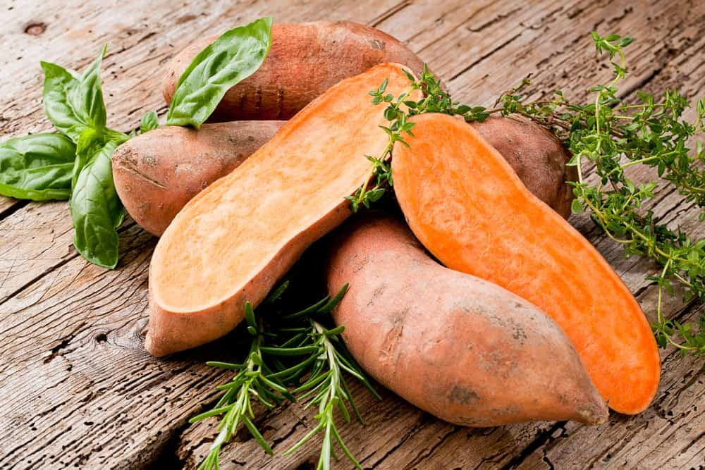 Pieces of sweet potatoes on a wooden table.