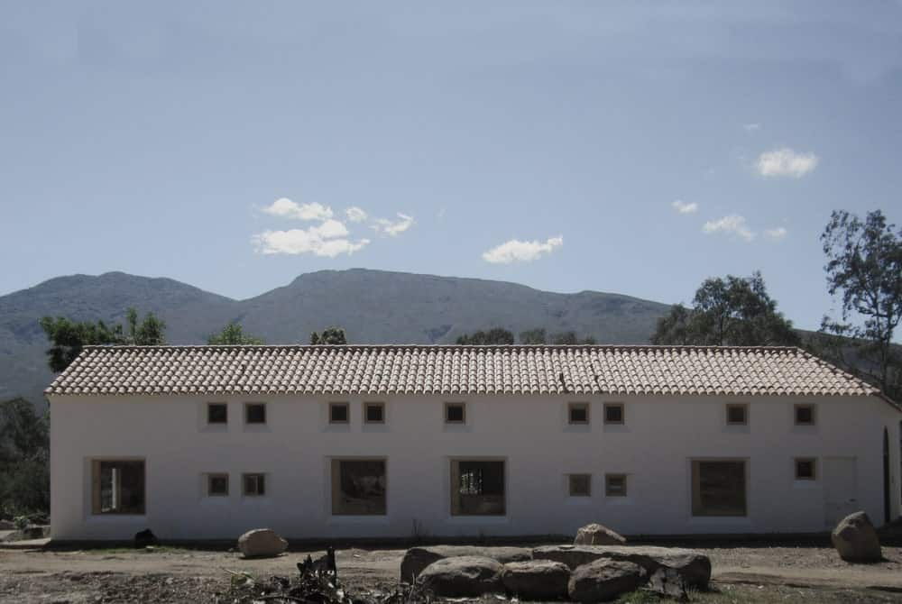 This is a full view of the house with adobe walls, red clay tiles on the roof and multiple small and large windows that stand out against the bright tone of the exterior walls.