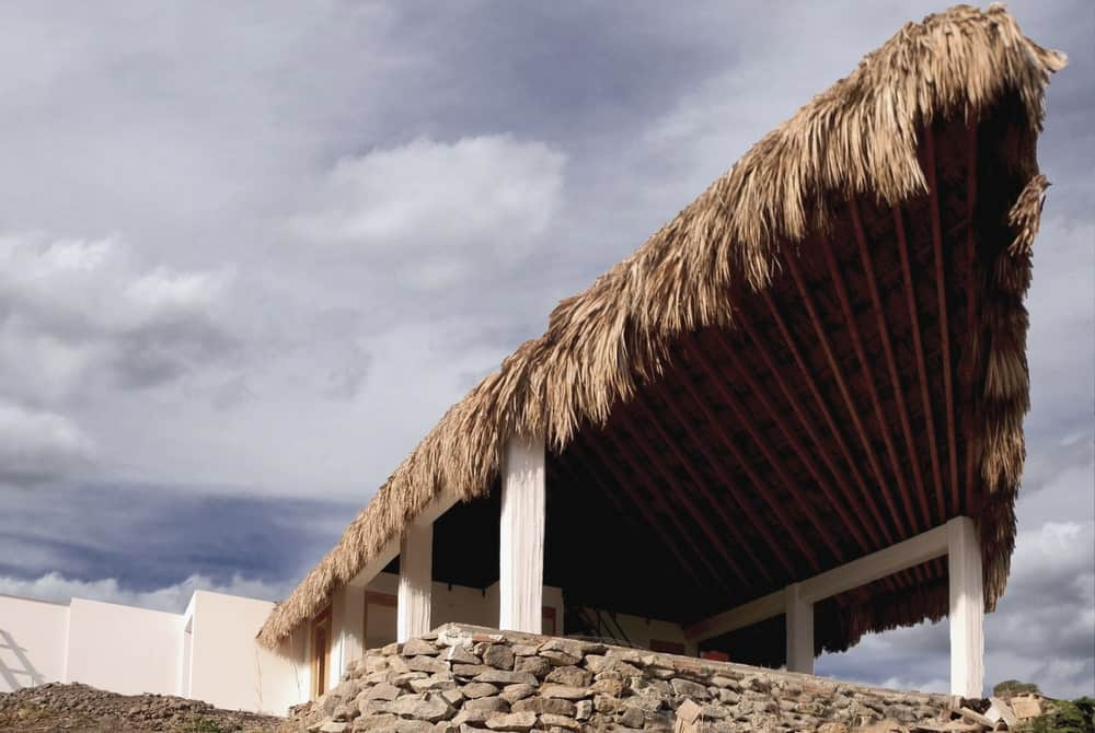 The white pillars that support the palm roof of the house stands on a large stone base.