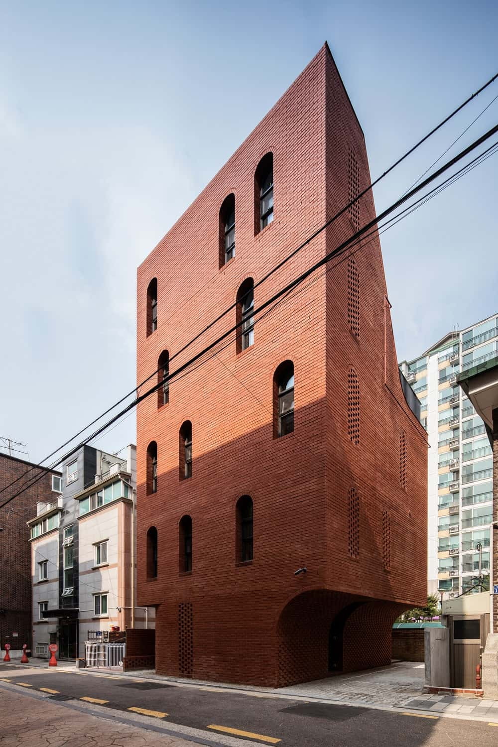 This side of the house showcases more of the unique shape of the red brick building with a cavernous area to make place for parking.