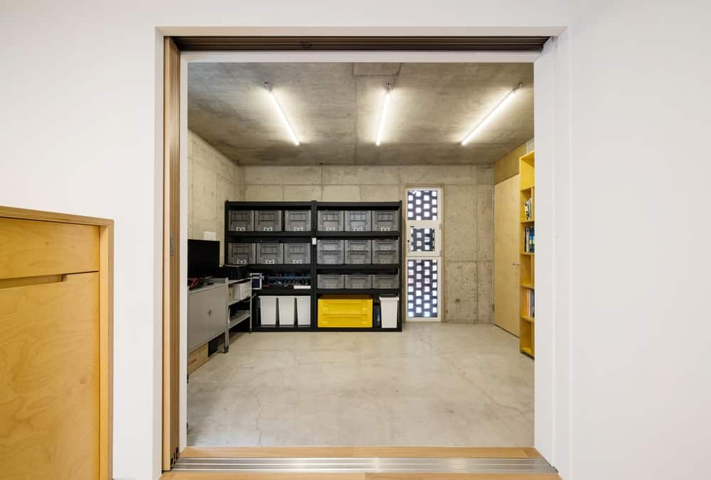 Upon entry of the main door, you are welcomed by this foyer and storage area with shelves and cabinets as well as a book shelf on the side.