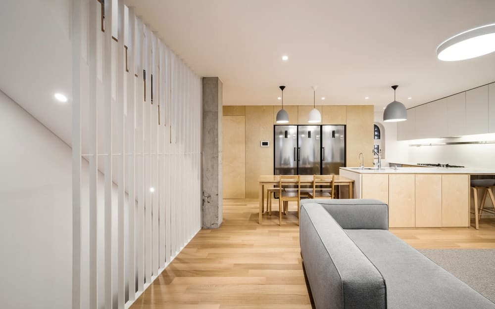 This is a view of the great room that houses the living room and the kitchen that has a kitchen island with an attached wooden table at the edge.