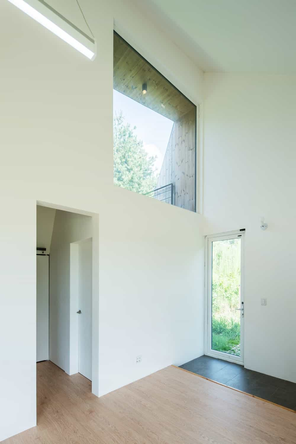 This is a look at the interiors of the house with bright white walls and a soaring ceiling.