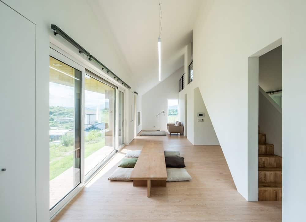 This is a look at the spacious and bright dining area with a low and long wooden table that matches with the flooring.
