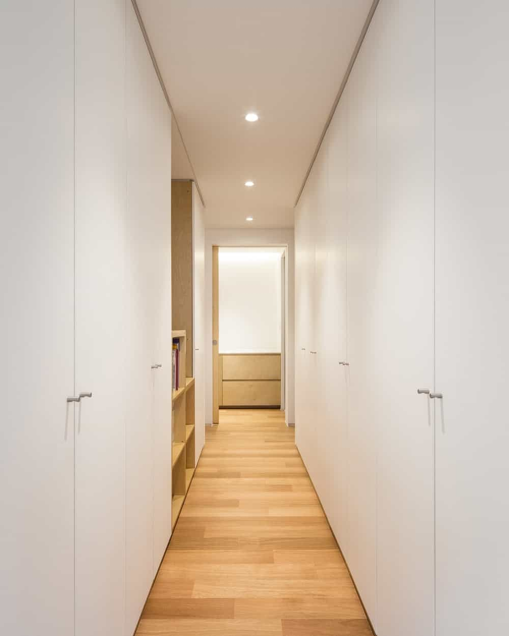 This is a hallway with hardwood flooring complemented by the flanking white walls and wooden shelves.