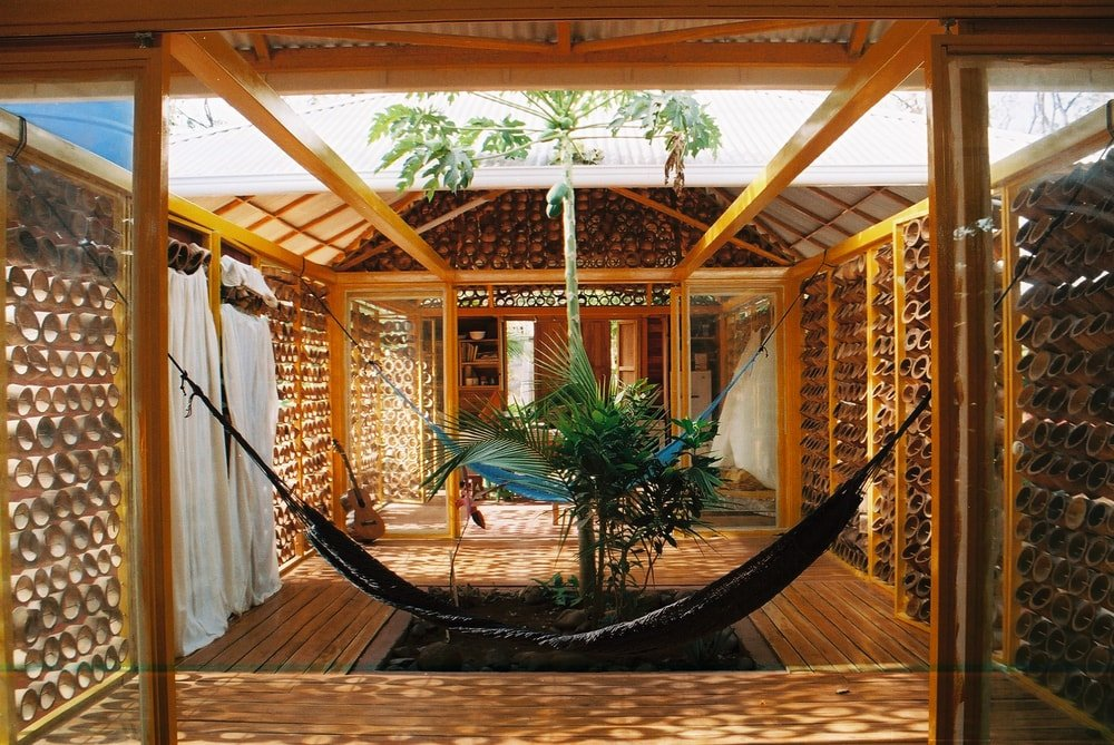 This is a close look at the middle part of the house with no roof, a papaya plant and a couple of hanging hammocks.