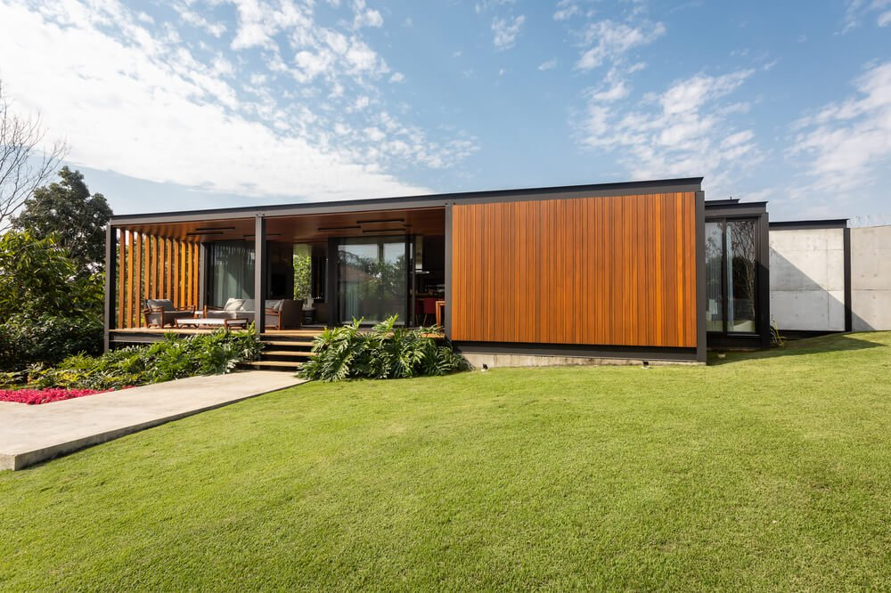 This is a look at the front of the house that has metal frames, wood exterior walls and large glass walls along with a covered porch area by the entrance.