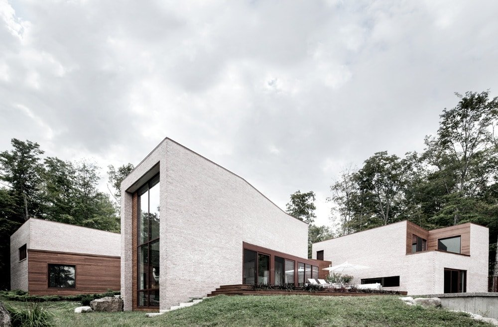 This is a side view of the house's elevation that seem to look like three separate structures with white exterior walls, wooden accents and large glass walls.