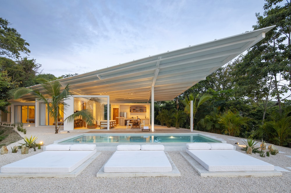 This is a view of the house from the vantage of the swimming pool that has three lounge day-beds on the side. The house has a large covered area next to its glass doors that is topped with a flat roof.
