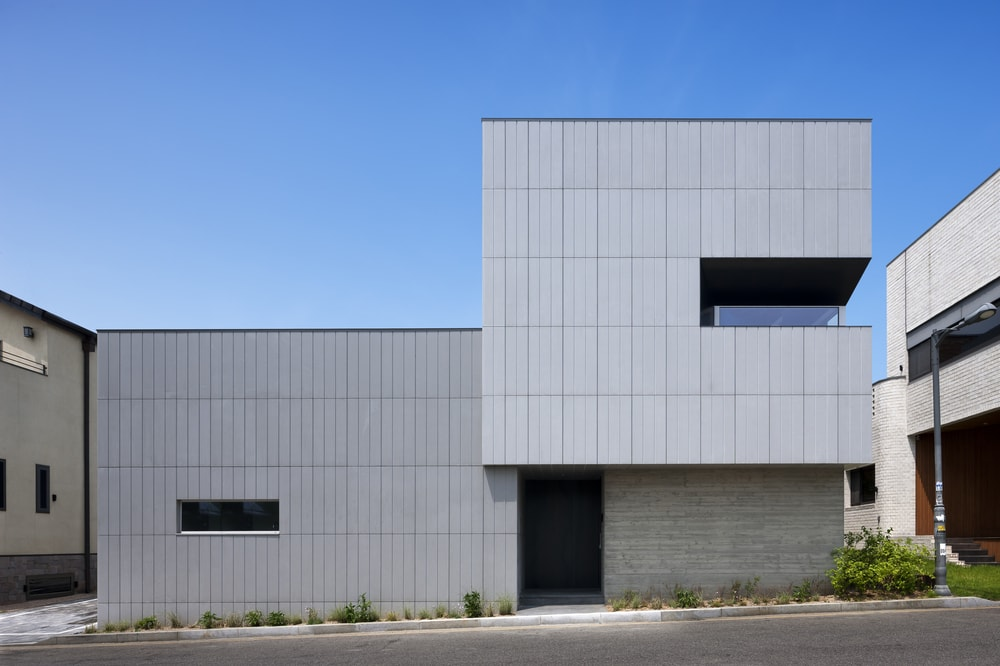 This is a front view of the minimalist house that has consistent light gray panels on its modern exterior walls complemented by the windows and the main entrance in the middle with a door in a covered area.