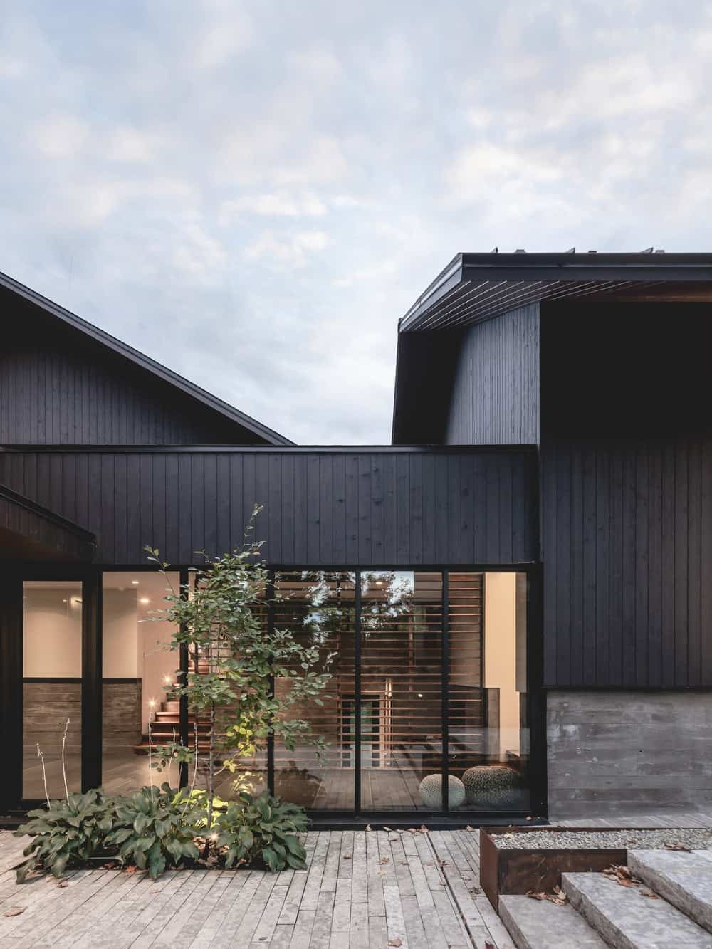 This is a side of the house with dark walls that make the glass walls stand out with warm glow from the interior lights.