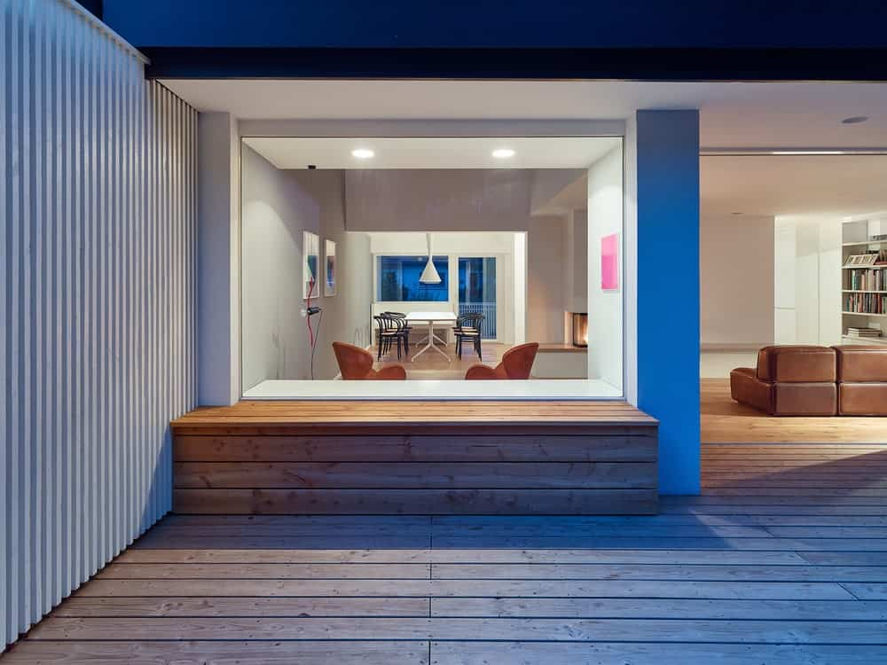 On the side of this patio is a built-in wooden bench that matches the wooden flooring. This has a view of the interior through a glass window.