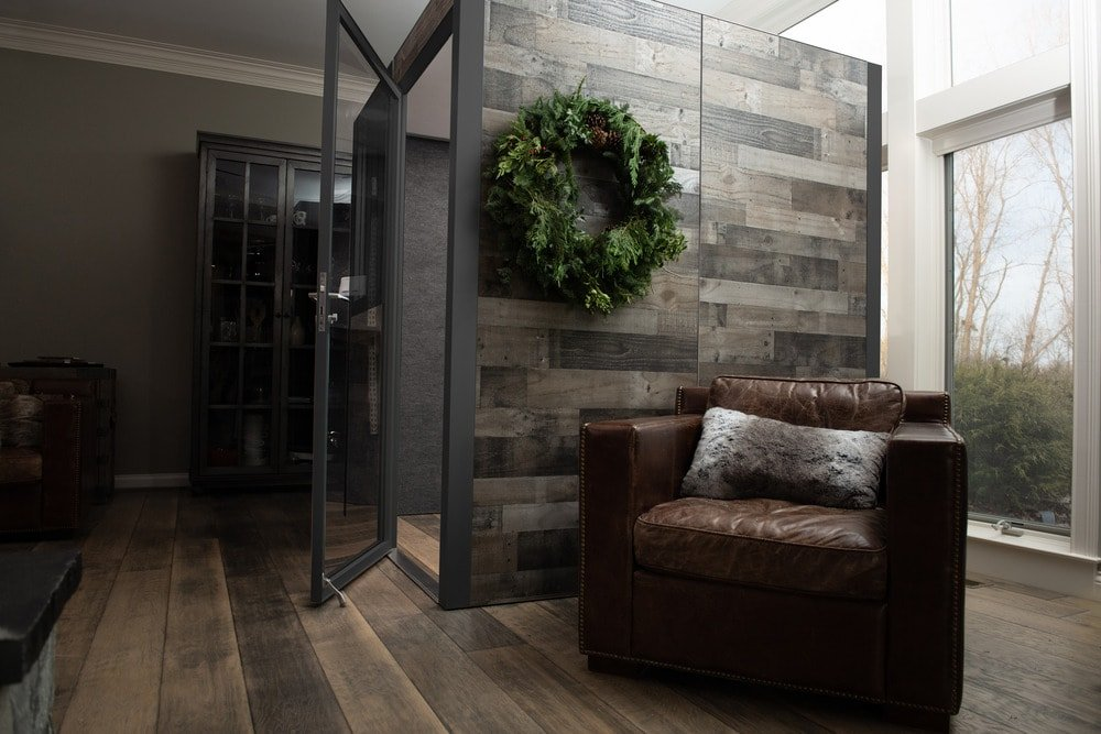 This is a look at the office pod that has a wooden wall on the side that matches well with the hardwood flooring decorated with a wreath.