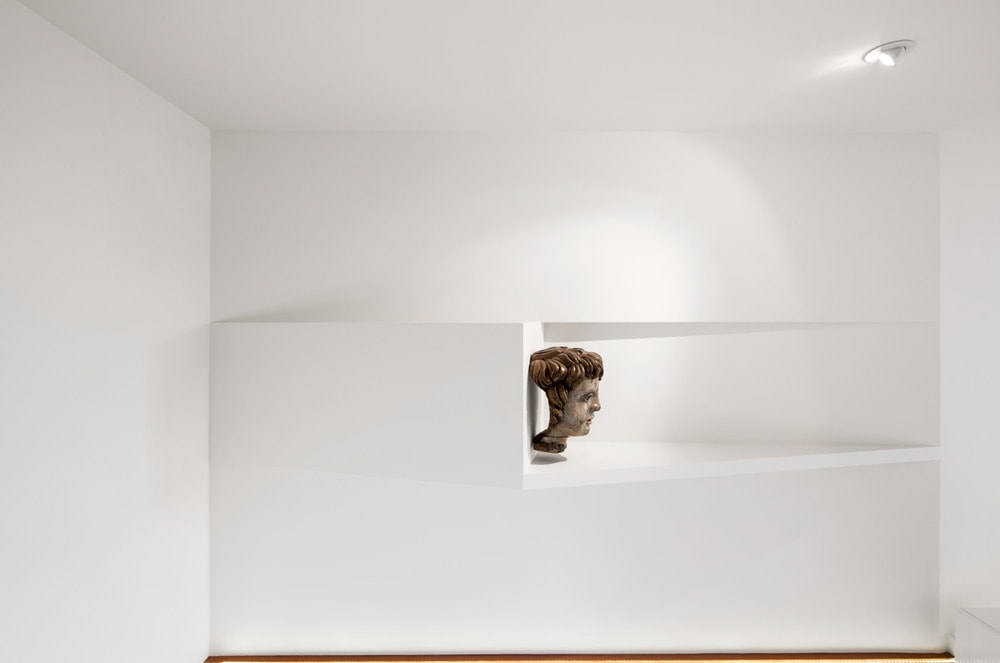 The white concrete beams above the stairs is adorned with a head sculpture display.