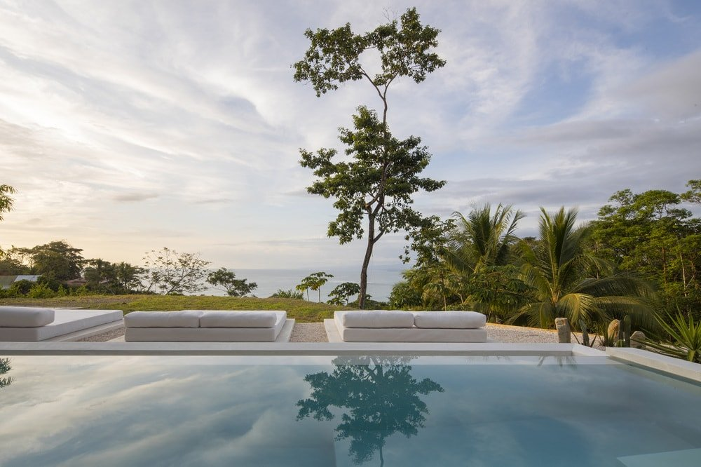 This is a close look at the infinity edge pool that has a few day beds on the side facing the landscape.