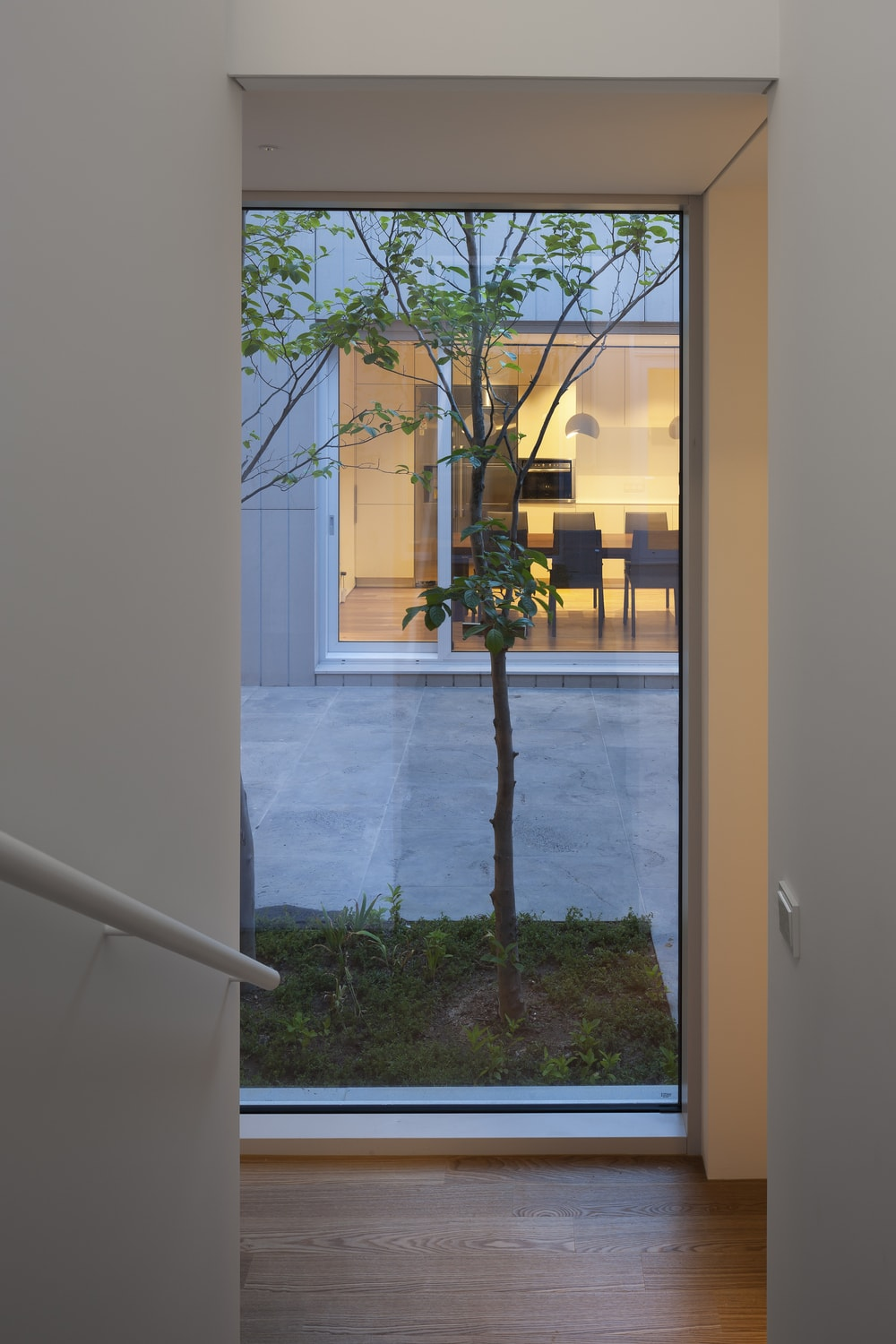This is a view from the vantage of the staircase inside through to the courtyard and across to the dining area through the glass wall.