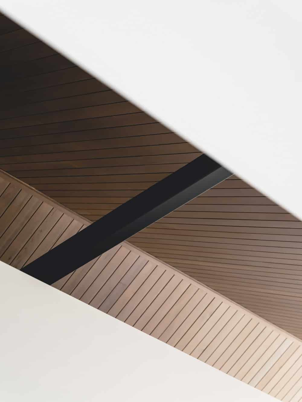 This is a close look at the tall wooden shiplap cathedral ceiling with a look at a single black beam.