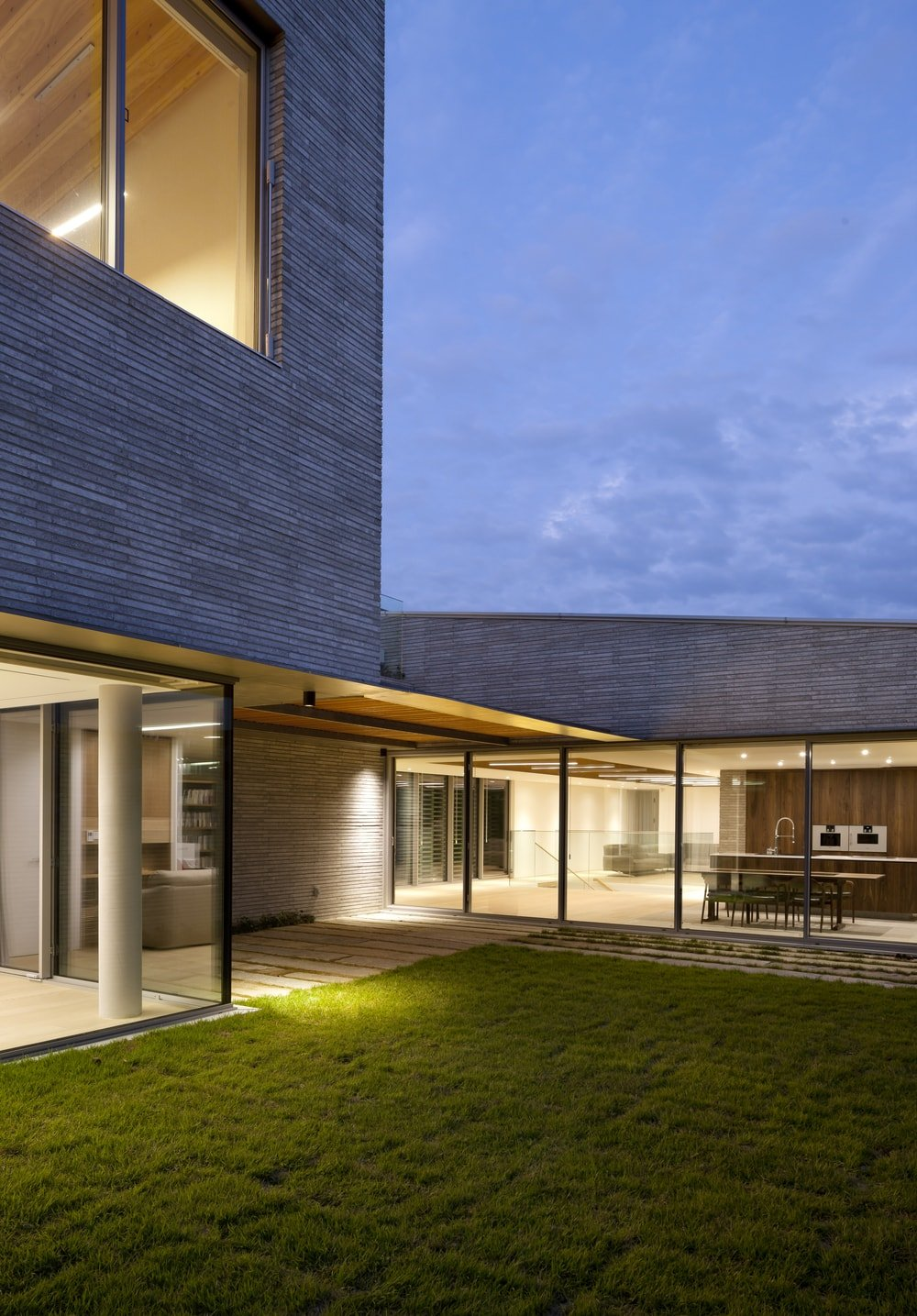 This is a nighttime view of the house walkways and glass walls giving the interior a seamless transition.