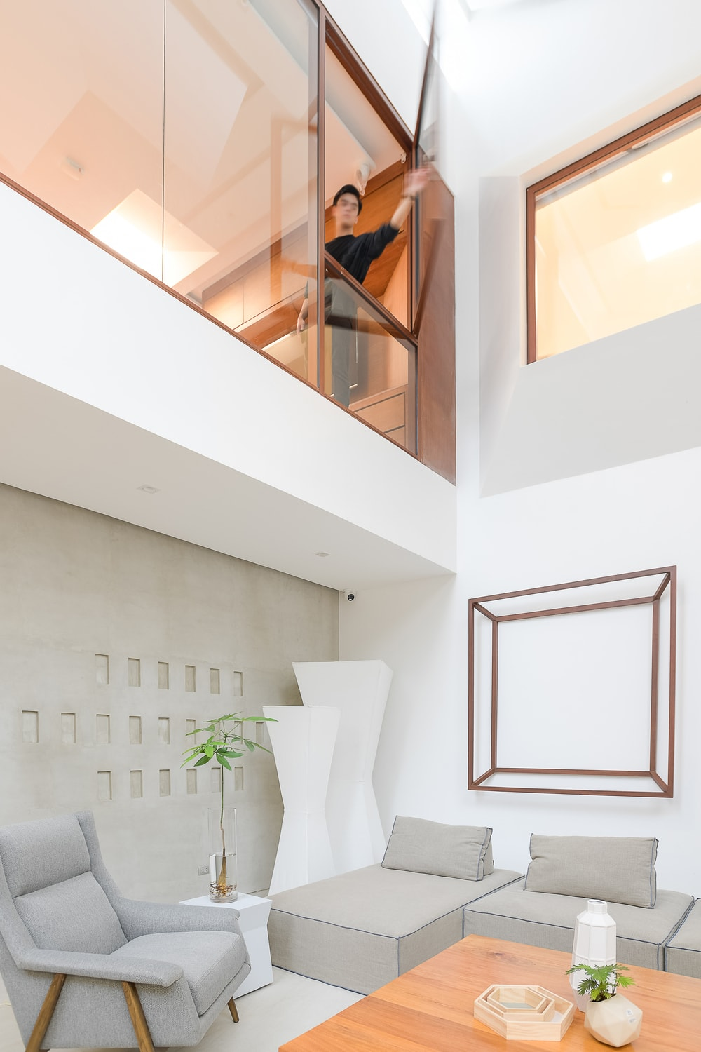 This is a closer look at the glass walls of the indoor balcony above the living room that has a window that can be opened.