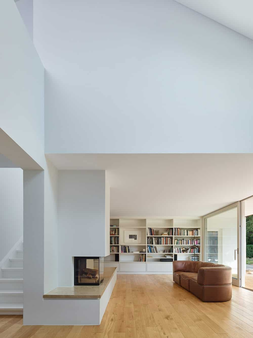 The bright white walls, ceiling and bookshelves of the living room are contrasted by the sectional sofa, fireplace and the books on display.