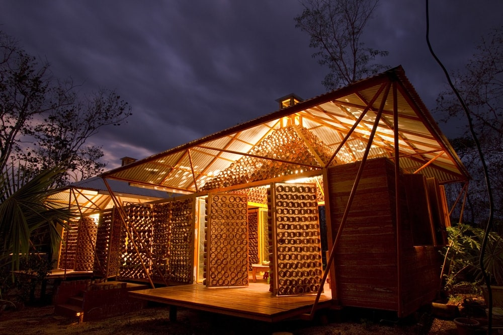This is a nighttime view of the house that has swiveling exterior wall panels that are made of mounted pieces of bamboo that can let in light.