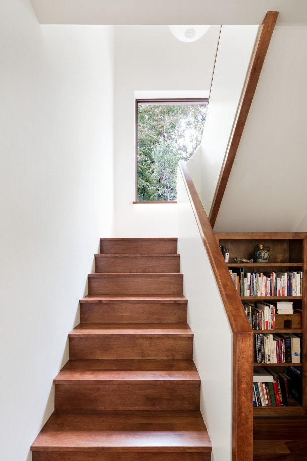This is a close look at the staircase with wooden steps to pair with the wooden built-in shelves on the side.