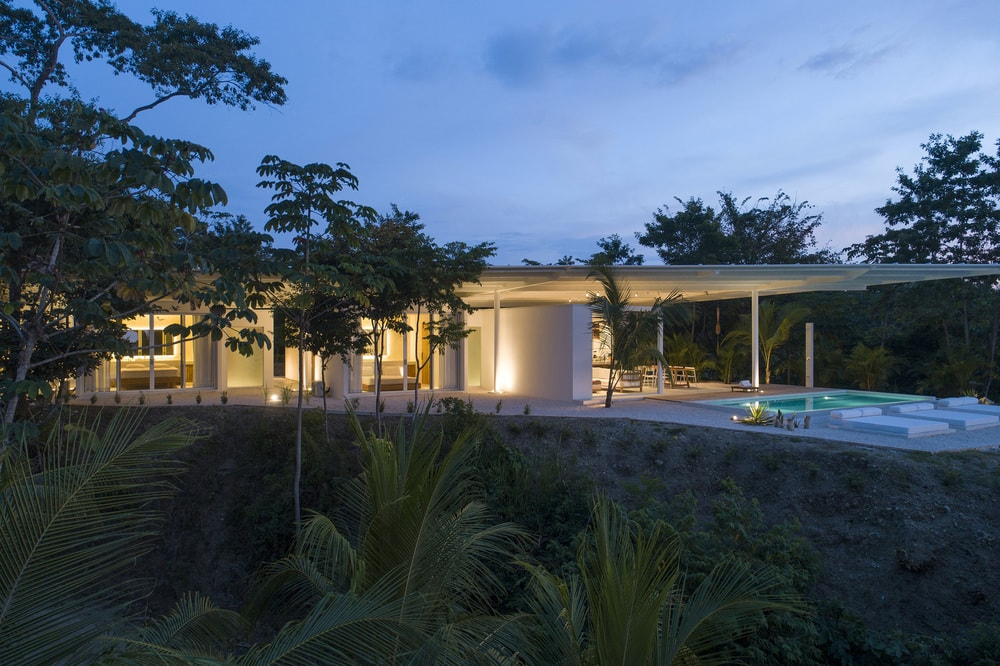 This is a nighttime view of the house showcasing the warm glow of the glass walls of the house coming from the interior lights.