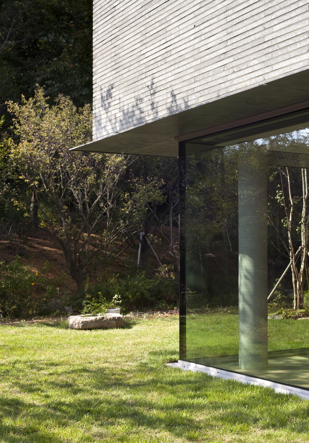 This is a close look at the corner of the glass wall in contrast with the grass lawn just outside.