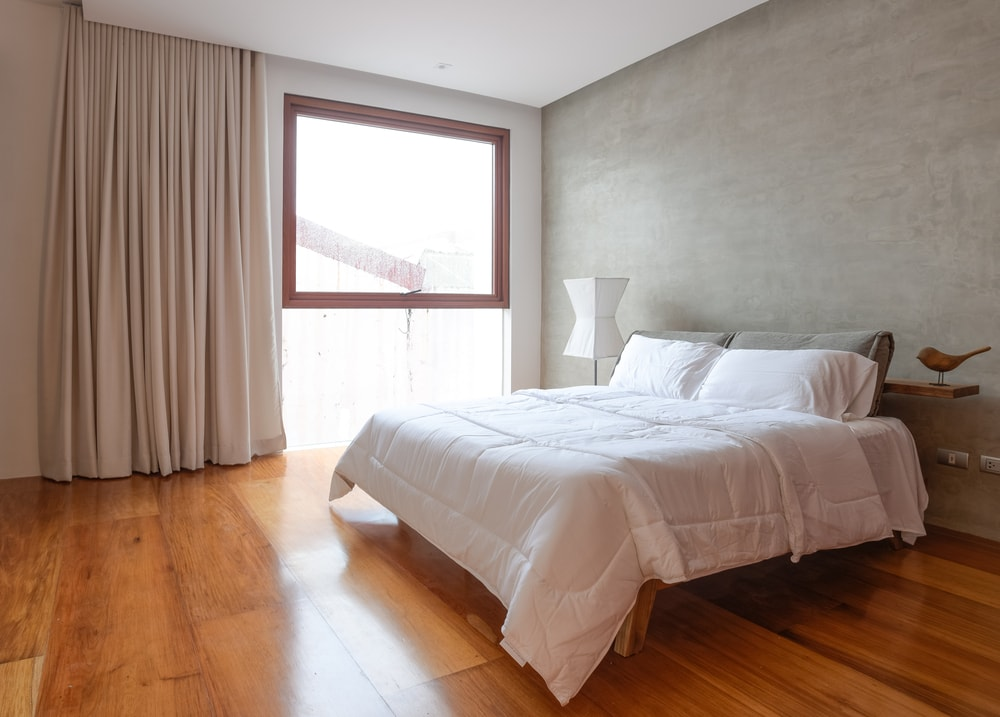 This other bedroom has a hardwood flooring that is brightened by the natural lighting of the window.