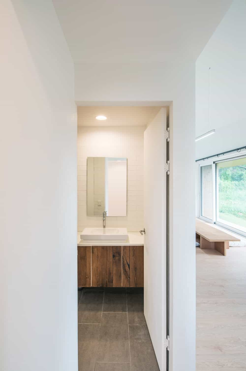 The bathroom has a brown wooden floating vanity with a wall-mounted mirror above.