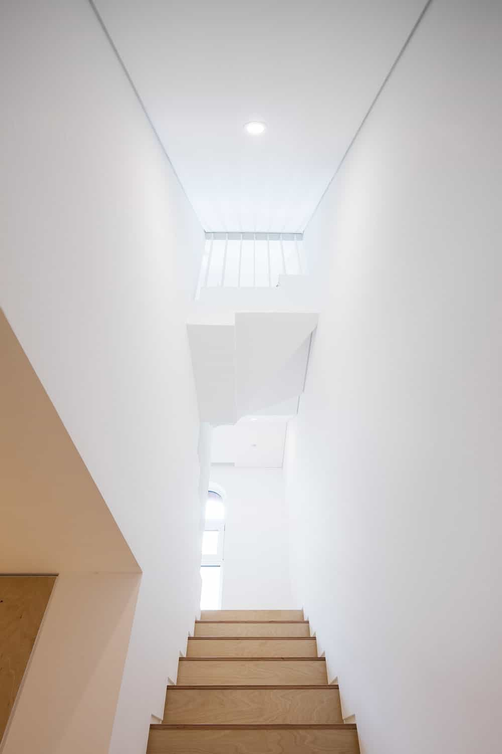 This is a look up the staircase showcasing the bright white walls above the stairs as well as the indoor balcony.