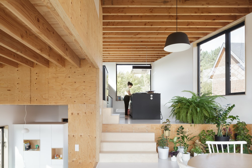 This is another look at the kitchen that has a large dark kitchen island underneath a alrge wooden beamed ceiling.