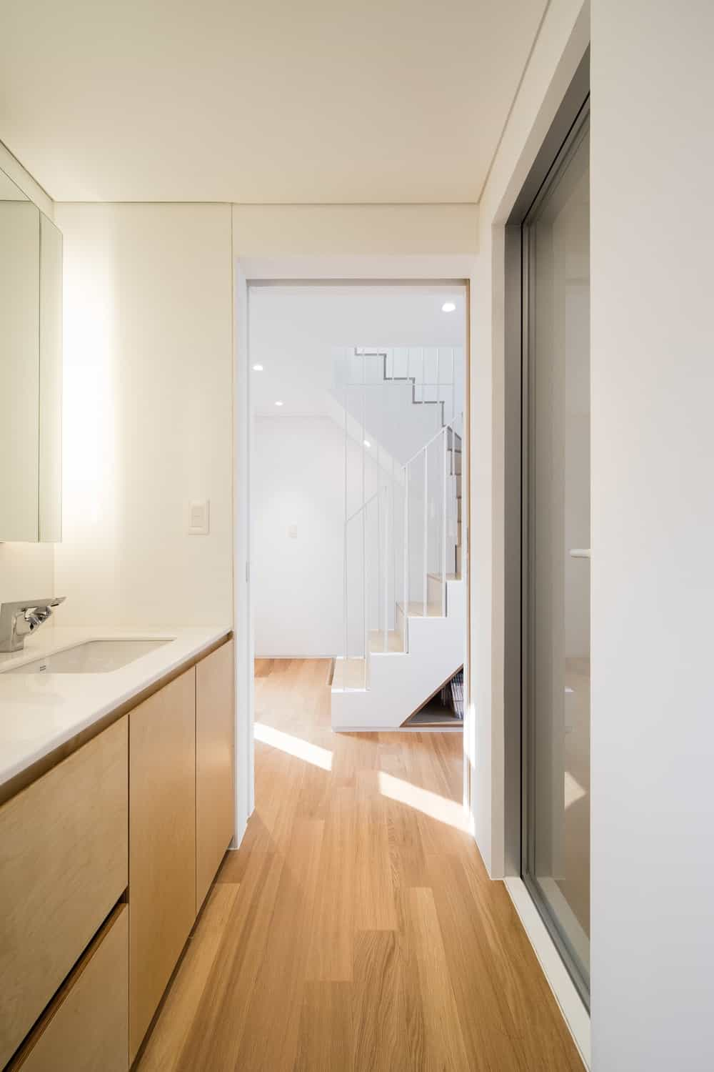The bathroom is by the staircase with a wooden cabinetry to its vanity across from the glass door of the shower area.