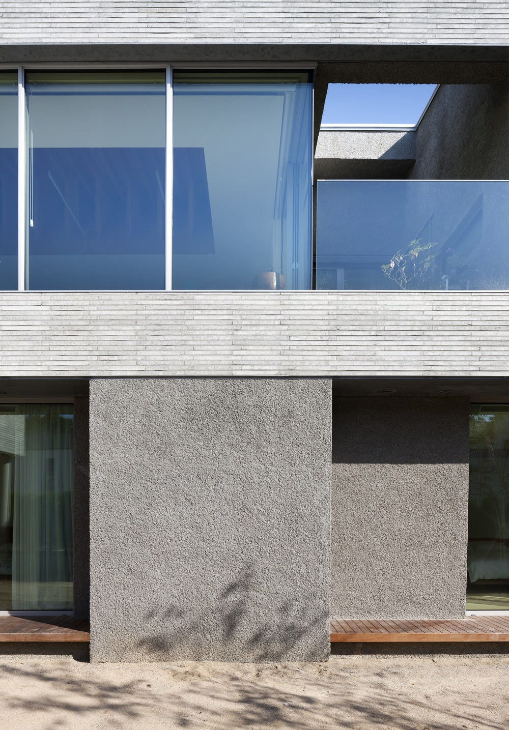 This is a close look at the exterior of the house showcasing the different tones and textures as well as the glass walls of the upper level.