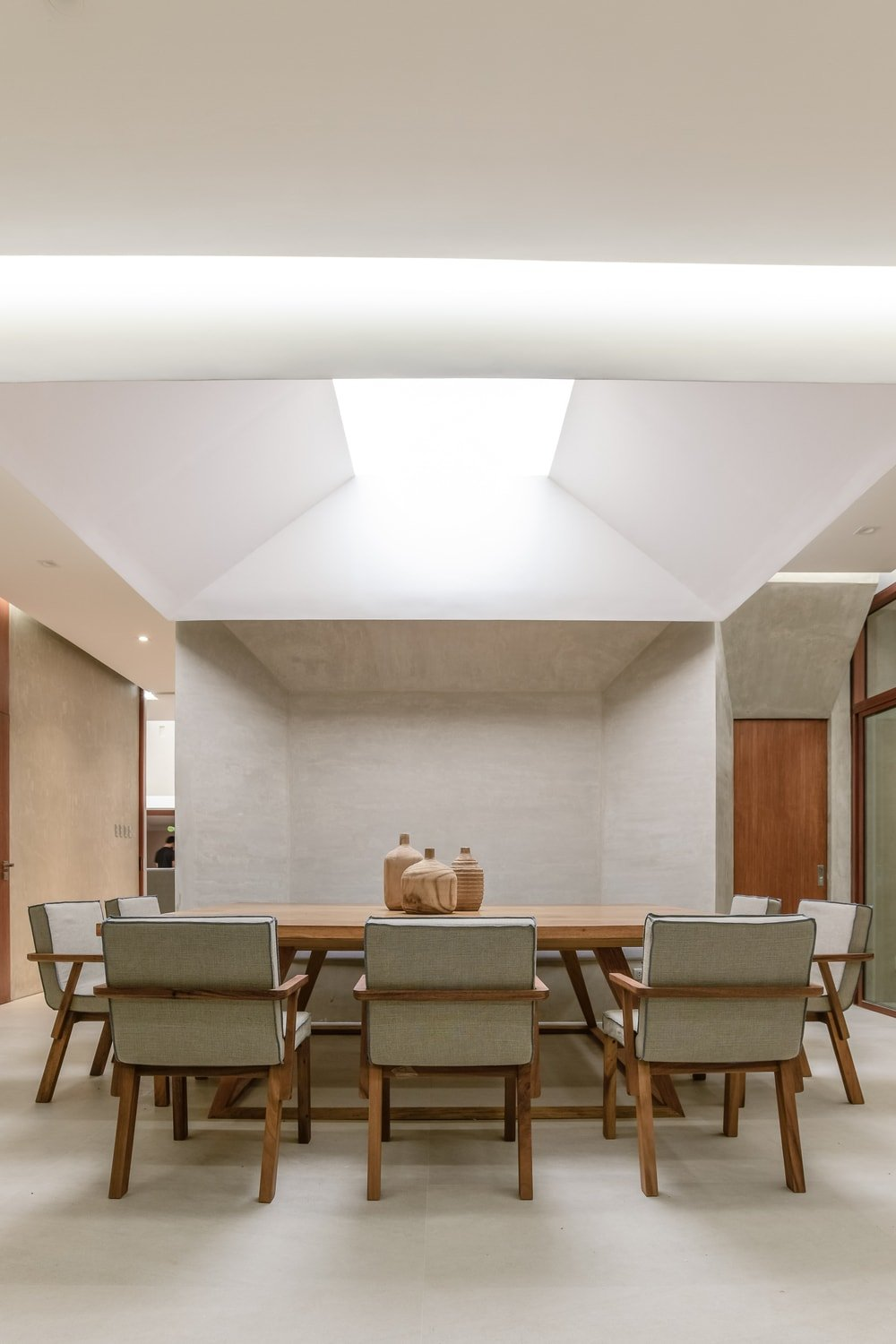 The dining set is topped with a cove ceiling that has a modern lighting in the middle.